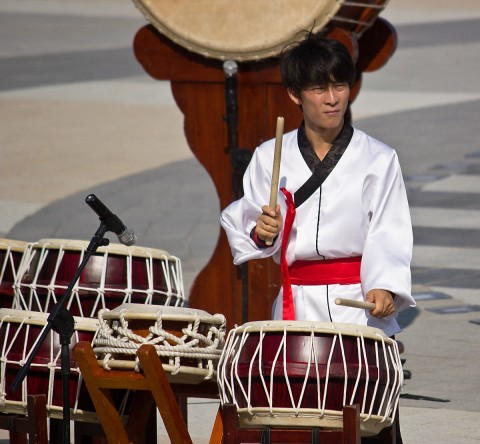 Young man playing Korean drums