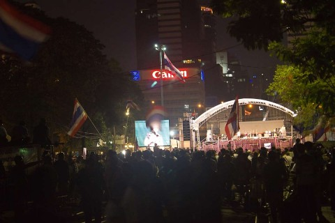 Night photo of crowd of protesters at Lumphini Park.